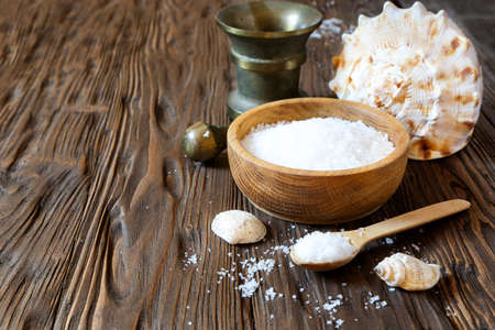 Sea salt in a wooden bowl on the table, space for text Stock Photo