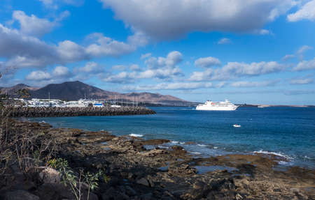 View from the shore of the ocean to the port of the village of Playa Blanca, Lanzarote Island, Canary Islands, Spain
