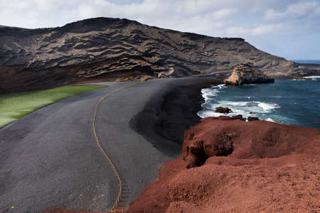 Green lagoon and black beach on the ocean shore at El Golfo volcano, the island of Lanzarote, Canary Islands, Spain