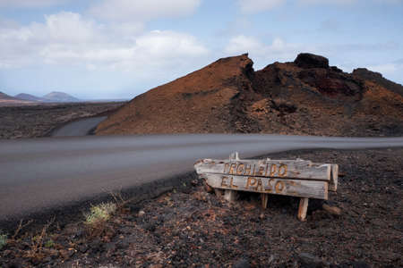 Old road sign in national volcanic park of Timanfaya, the island of Lanzarote, Canary Islands, Spain