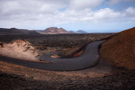 Lava fields and road in the territory of the national volcanic park of Timanfaya, the island of Lanzarote, Canary Islands, Spain