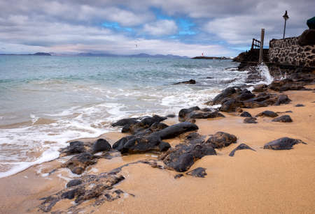 Sea and rocks on the city beach in the village of Playa Blanca,