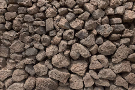 Background -  wall composed of lumps of volcanic lava Stock Photo