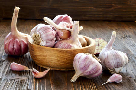 Garlic in a wooden bowl on the kitchen table