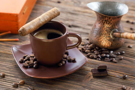 Zigarre, Schokolade und eine Tasse schwarzen Kaffee auf einem Holztisch Standard-Bild