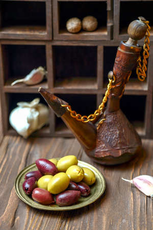 Olives in a bronze plate and  old jug with oil on a wooden kitchen table