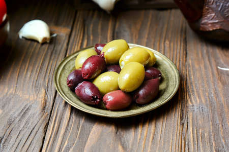 Olives in a bronze plate  on the kitchen table, close-up