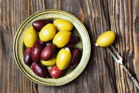 Olives in a bronze plate  on the kitchen table, top view