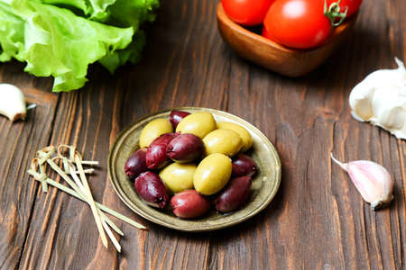Olives in a bronze plate and fresh vegetables on the kitchen table Фото со стока
