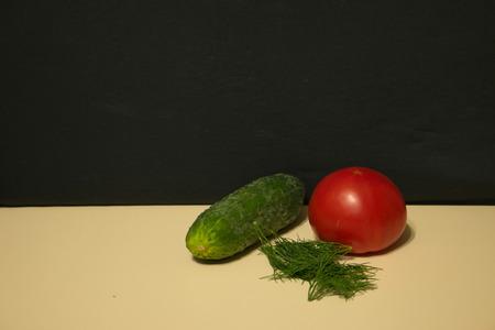 Cucumber tomato fennel light table dark background