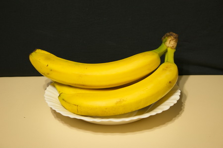 Bunch of bananas light table dark background in a plate