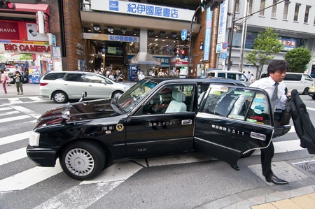 TOKYO, JAPAN, JULY 5: unidentified person out of a taxi in Shinjuku district on July 5, 2011 in Tokyo, Japan. Tokyo is estimated that there are around 35,000 taxi drivers are divided into 33 different companies. Typically, taxis are Toyota Crown Comfort.