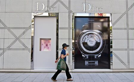 TOKYO, JAPAN - JULY 6: woman walking by the window of Dior in Ginza, one of the most glamorous in Tokyo
