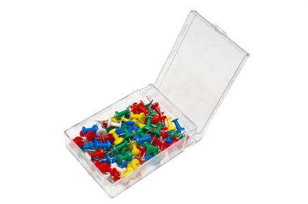 Colored thumbtacks in a box on white background photo