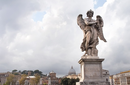 Famous statues San Angelo Bridge in the background with the Vatican in Rome, Italy photo