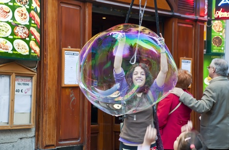 MADRID, SPAIN-27 NOVEMBER: unidentified girl making huge bubbles in the street to the amusement of the tourists on November 27, 2011 in Madrid, Spain.    A soap bubble is a very thin film of soap water that forms a hollow sphere, and exhibits an iridescen Stock Photo - 11653856