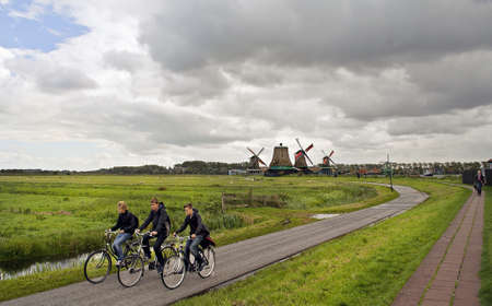 volendam: VOLENDAM, NETHERLANDS, SEPTEMBER 17: Unidentified cyclists walking Volendam on September 17, 2010