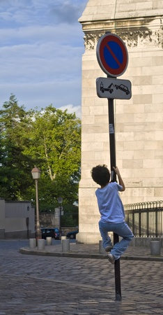 Child climbing up a traffic signal photo