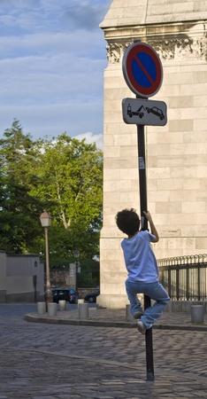 Child climbing up a traffic signal photo