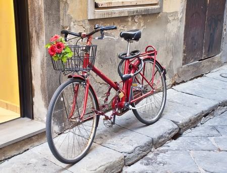 retro bicycle: Moto retro en rojo con un ramo de flores en la canasta Foto de archivo