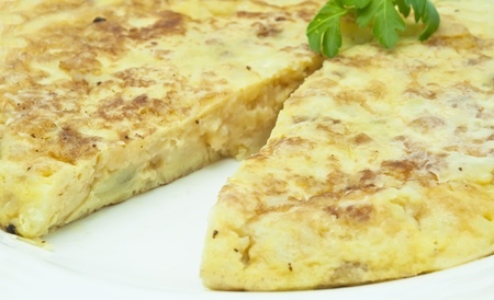 Spanish potato omelet on a dish on white background photo