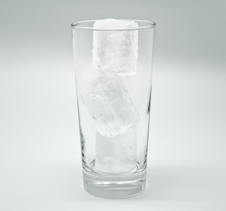 Empty glass with ice in gray photo