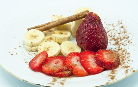 Strawberries and banana dish garnished with cinnamon sticks and ground cinnamon photo