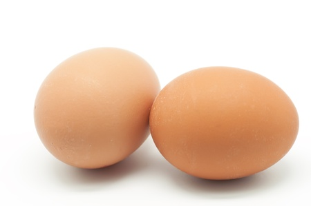 chicken or egg: Two raw eggs on white background Stock Photo