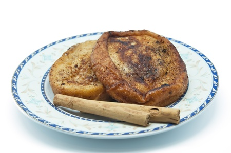 Several torrijas on a plate on white background. The torrijas or toast is a typical sweet of the celebrations of Lent and Holy Week in Spain photo