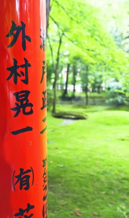 Pole with Japanese inscription in the foreground in a Japanese forest Stock Photo - 13848606