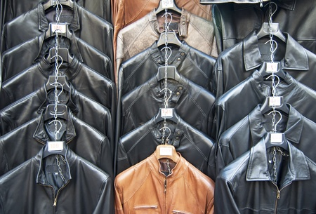 Many leather jackets hanging in shop photo