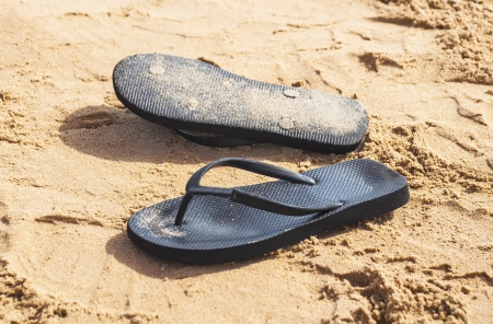 Summer Sandals in the sand on the beach photo
