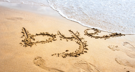 Bye written in the sand on the beach  Stock Photo
