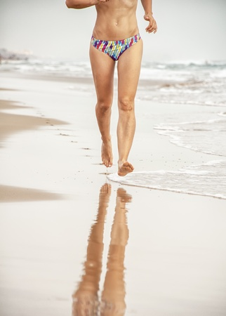 Girl running on the beach with reflection in water Stock Photo - 14966444
