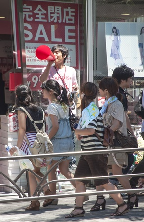TOKYO, JAPAN-SEPTEMBER 10: unidentified seller in the door of a clothing store advertising offers and products to people in the Shibuya district on September 10, 2011 in Tokyo, Japan