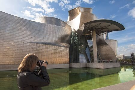 BILBAO, SPAIN - OCTOBER 13: Woman taking a picture at the Guggenheim Museum on october 13,2012 in Bilbao,Spain. The Guggenheim is a museum of modern and contemporary art designed by Canadian-American architect Frank Gehry.