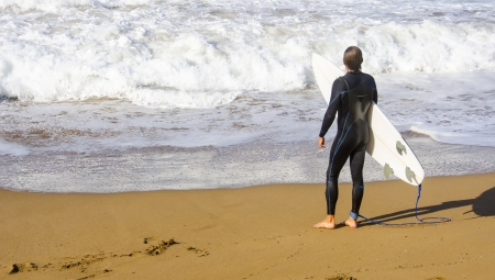 Surfer waiting in the sand at the beach surfing Zarautz