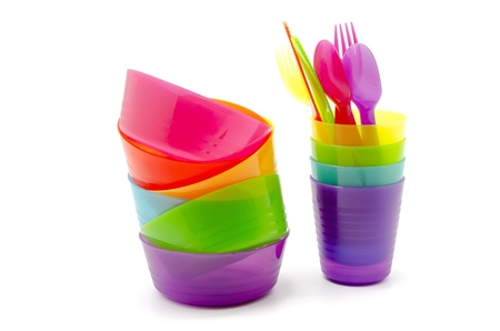 Plastic tableware of various colors on white background photo