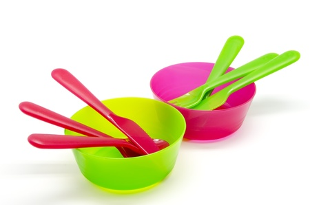 Plastic tableware green and pink on a white background photo