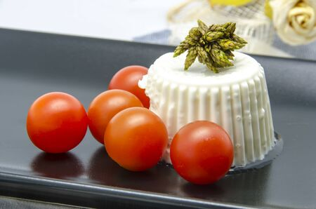 Fresh cheese with cherry tomatoes on a black plate photo