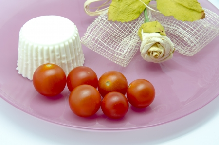 Fresh cheese with cherry tomatoes on a plate with decoration photo