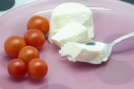Fresh cheese with cherry tomatoes with a spoon photo