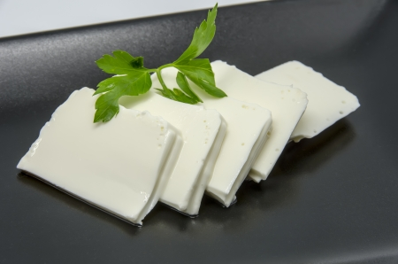 Fresh cheese   on a black dish photo