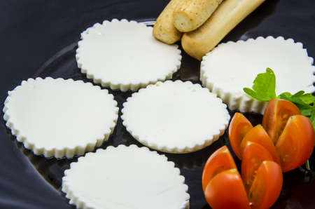 Fresh cheese with cherry tomatoes on a black dish photo
