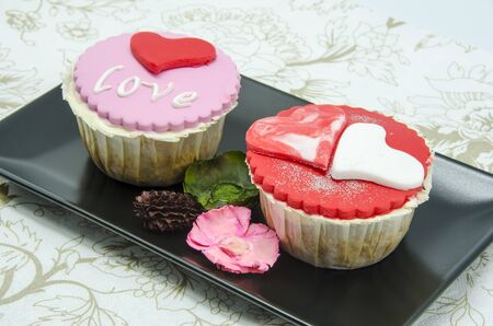 fondant fancy: Gourmet cupcakes with hearts and decorations Stock Photo