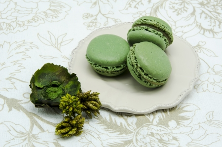 Green macaroons on a tablecloth and decorations photo