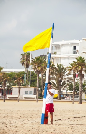 GANDIA, SPAIN-JULY 26: Rescue Lifeguard placing the yellow caution flag on the beach on July 26.2012 in Gandia, Spain. With caution the bathroom is not advisable, either by the sea state or by the presence of jellyfish in the water