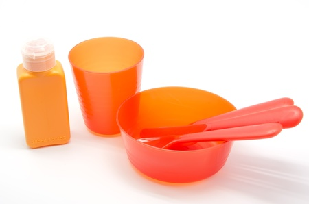 Plastic tableware orange on white background photo