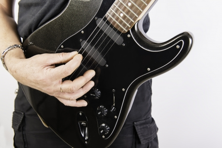 rock guitarist: Man playing a black guitar on white background