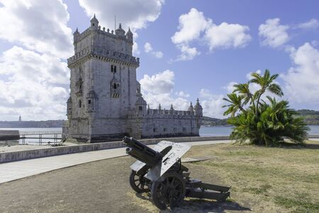 View a Belem tower with a cannon on a cloudy day photo